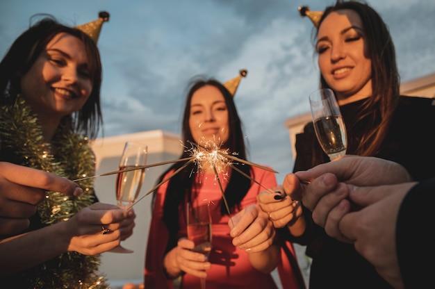 Grupo de mujeres fiesteras iluminando las bengalas