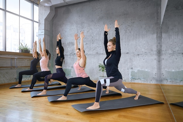 Grupo de mujeres fitness estiramientos sobre esteras.