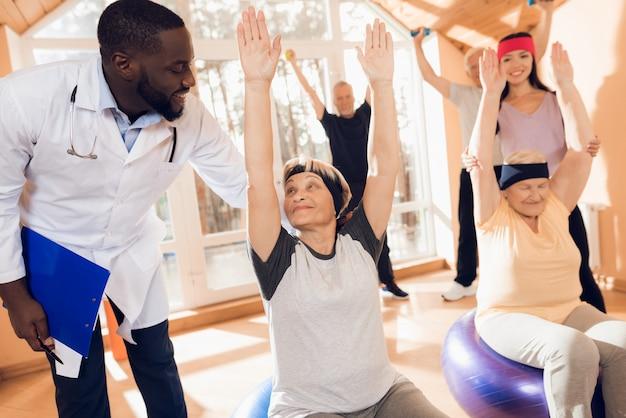 Grupo de mujeres y hombres de edad avanzada que realizan gimnasia terapéutica.