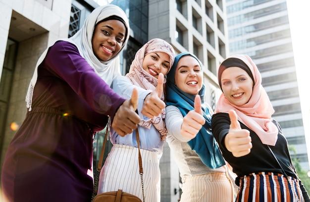 Grupo de mujeres islámicas gesticulando golpes arriba