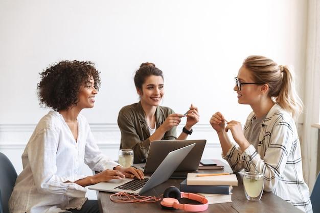 Grupo de mujeres jóvenes alegres multiétnicas que estudian juntos en la cafetería.