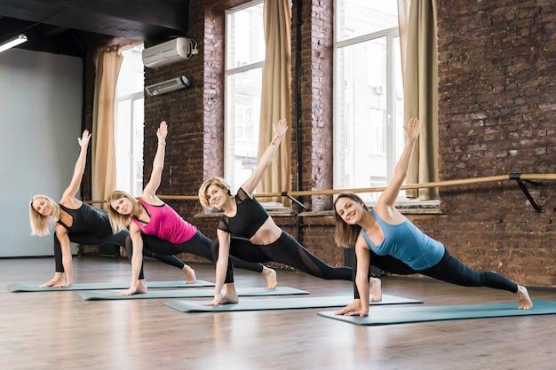 Grupo de mujeres jóvenes entrenando juntas en el gimnasio