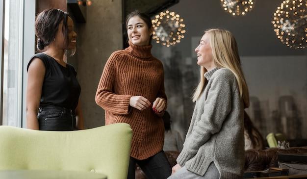 Grupo de mujeres jóvenes hablando entre sí en casa