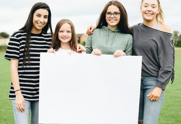 Grupo de mujeres jóvenes mostrando un tablero en blanco