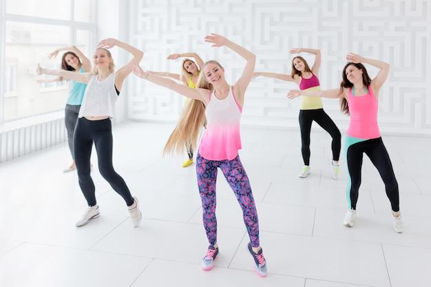 Grupo de mujeres jóvenes posando con los brazos levantados mientras toma una clase de baile de fitness