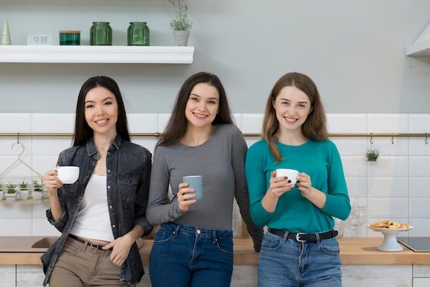 Grupo de mujeres jóvenes positivas con tazas de café
