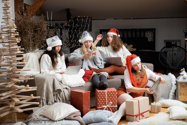 Grupo de mujeres jóvenes con sombreros navideños que usan teléfonos portátiles hacen videollamadas de saludo en la época navideña
