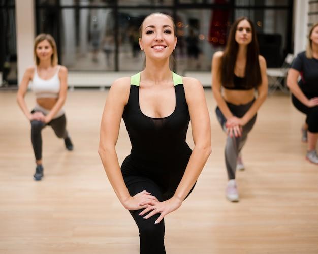 Grupo de mujeres jóvenes trabajando en el gimnasio.