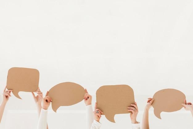 Grupo de mujeres manos sosteniendo burbujas de chat