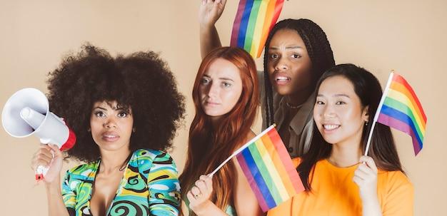 Grupo de mujeres multirraciales, con bandera del orgullo gay lgbt
