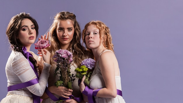 Grupo de mujeres posando con flores y espacio de copia