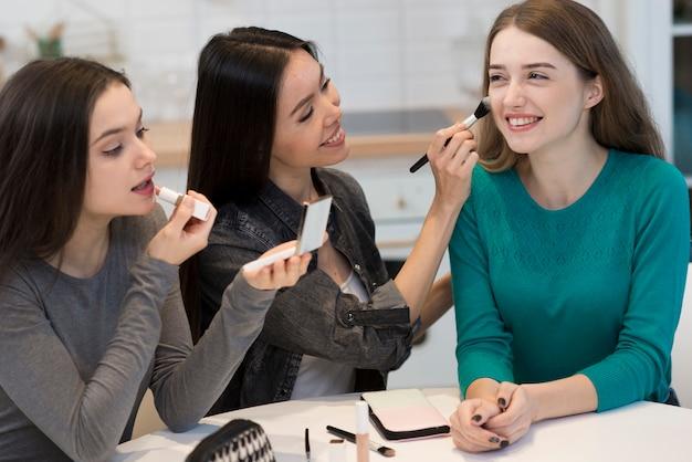 Grupo de mujeres positivas probando accesorios de maquillaje