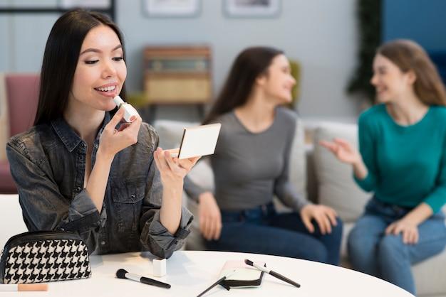Grupo de mujeres probando accesorios de maquillaje