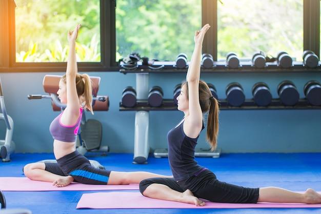 Grupo de mujeres que hacen yoga en gimnasio público de la aptitud