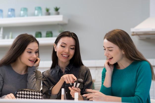 Grupo de mujeres revisando accesorios de maquillaje