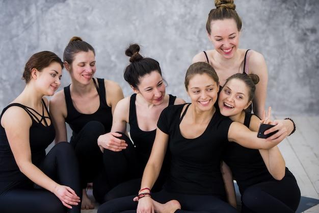 Grupo de mujeres sentadas y relajantes después de una larga clase de yoga y tomar selfie