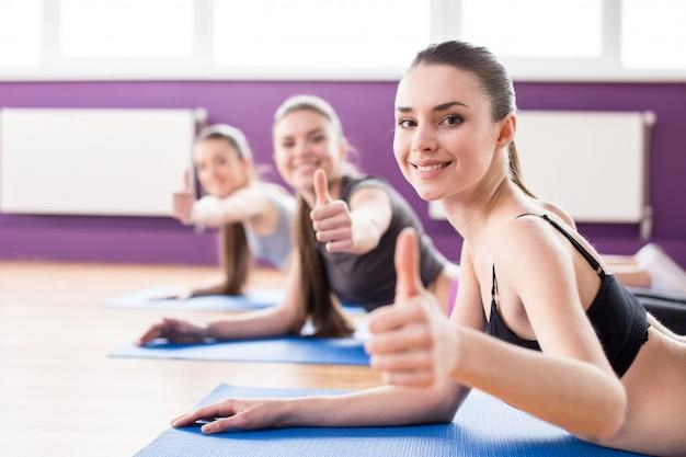 Grupo de mujeres sonrientes activas están entrenando en el gimnasio.