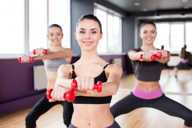 Grupo de mujeres sonrientes están estirando en el gimnasio.