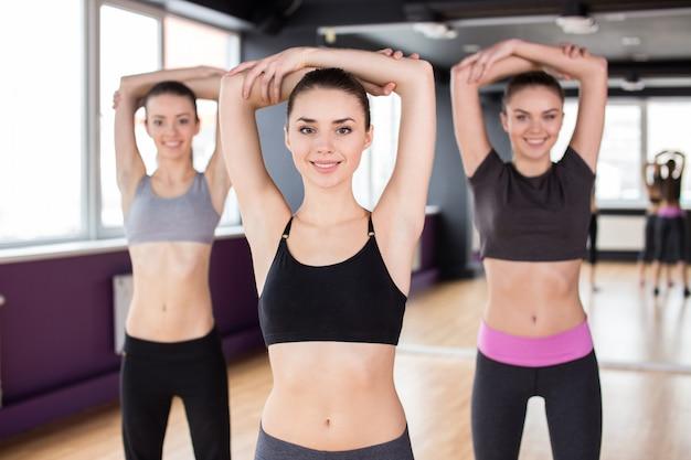 Grupo de mujeres sonrientes se estiran en el gimnasio.