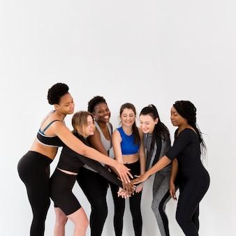 Grupo de mujeres terminando hacer ejercicio con apretón de manos