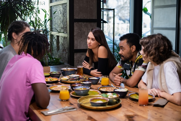 Un grupo multicultural de jóvenes en un café, comiendo comida asiática, bebiendo cócteles, conversando