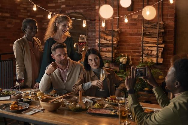 Grupo multiétnico de alegres personas adultas que toman fotos mientras disfrutan de la fiesta con iluminación exterior