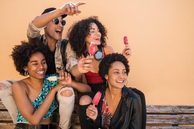 Grupo multiétnico de amigos disfrutando del verano mientras comen helado.
