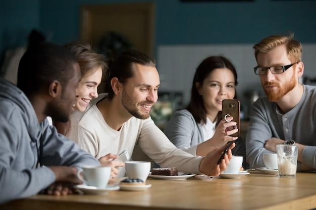 Grupo multiétnico de amigos hablando y usando teléfonos inteligentes en la reunión