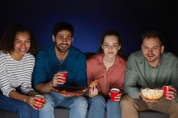 Grupo multiétnico de amigos viendo películas en casa mientras comen bocadillos y palomitas de maíz sentados en un sofá grande en una habitación oscura