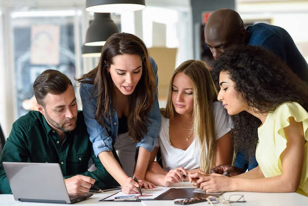 Grupo multiétnico de hombres jóvenes y de mujeres que estudian adentro.