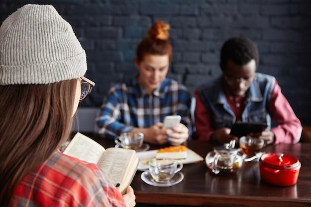 Grupo multiétnico de elegantes jóvenes estudiantes bebiendo té en el café durante las vacaciones: mujer con sombrero leyendo un libro mientras pelirroja mujer y hombre africano con aparatos electrónicos.