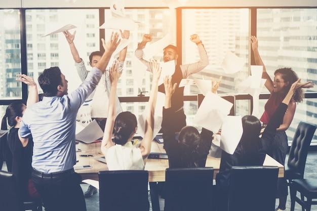 Grupo multiétnico de gente de negocios joven que lanza documentos y que parece feliz
