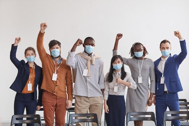 Grupo multiétnico de gente de negocios con máscaras y vítores mientras está de pie en fila contra el blanco en la sala de conferencias