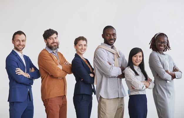 Grupo multiétnico de gente de negocios mirando a la cámara mientras está de pie en fila con los brazos cruzados contra el fondo blanco.