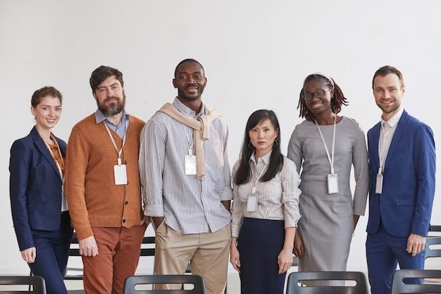 Grupo multiétnico de gente de negocios mirando a la cámara mientras está de pie en fila contra el blanco en la sala de conferencias