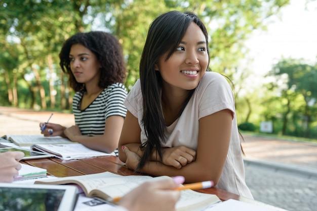 Grupo multiétnico de jóvenes estudiantes sentados y estudiando