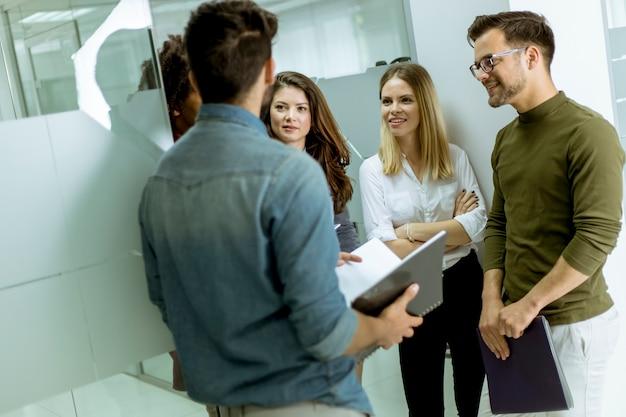 Grupo multiétnico de jóvenes de pie en la oficina moderna y de intercambio de ideas