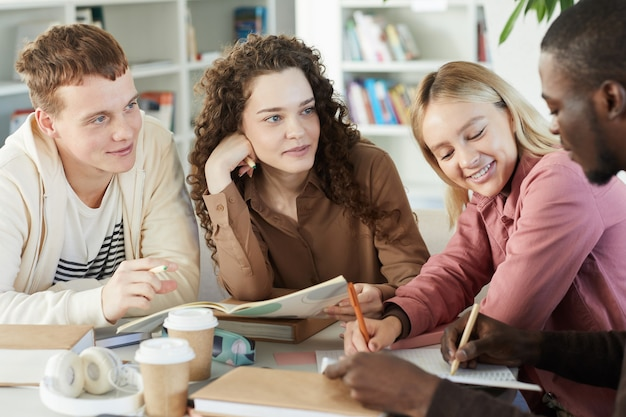 Grupo multiétnico de jóvenes sonrientes que estudian juntos mientras están sentados a la mesa en la biblioteca de la universidad y trabajan en un proyecto grupal