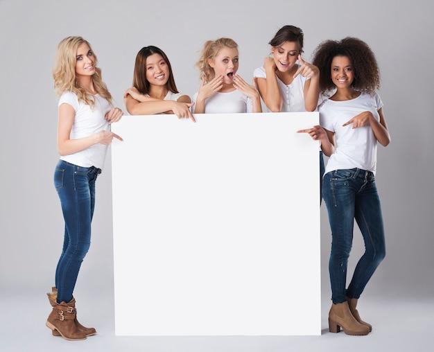 Grupo multiétnico de mujeres con pizarra vacía