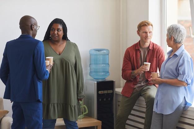 Grupo multiétnico de personas bebiendo café y charlando mientras está de pie junto al enfriador de agua en la reunión de apoyo, espacio de copia