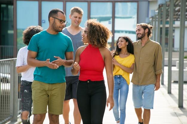 Grupo multiétnico de personas en caminatas casuales en entornos urbanos.