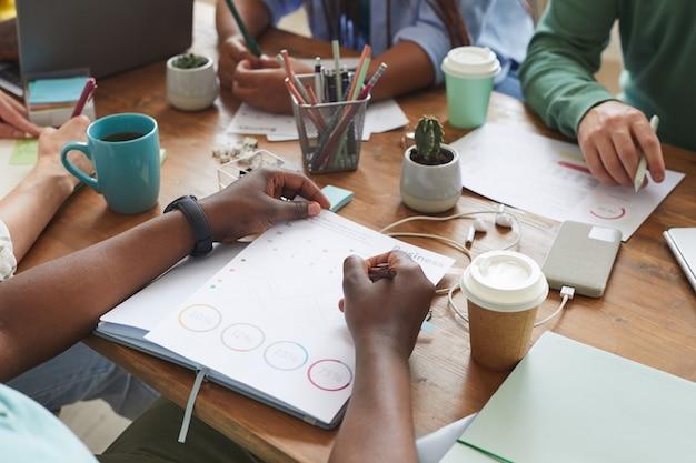 Grupo multiétnico de personas que trabajan juntas en una mesa desordenada con tazas, tazas y artículos estacionarios, trabajo en equipo o concepto de estudio