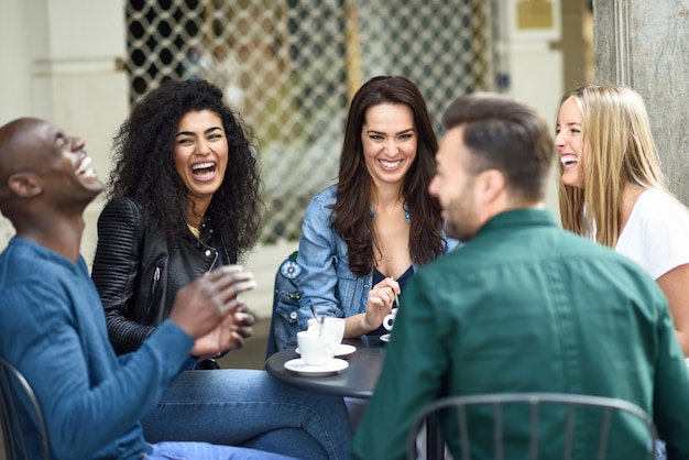 Grupo multiracial de cinco amigos que toman un café junto