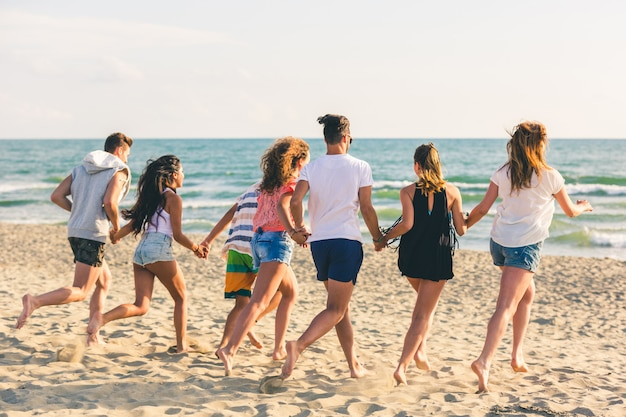 Grupo multirracial de amigos corriendo en la playa.