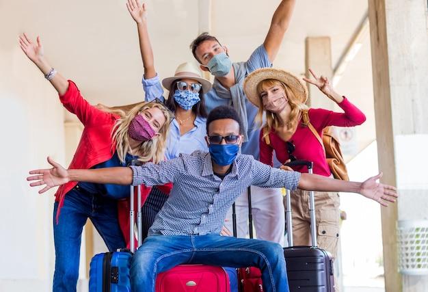 Grupo multirracial de amigos en la estación de tren con equipaje con máscara protectora