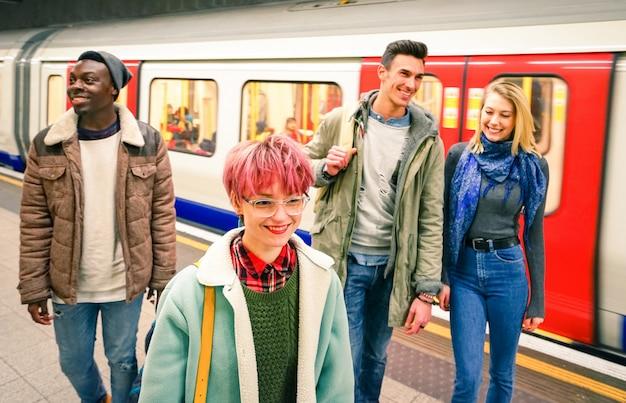 Grupo multirracial de amigos hipster divirtiéndose en la estación de metro