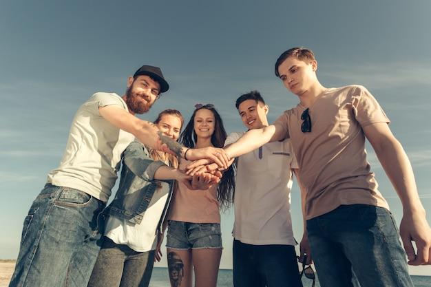 Grupo multirracial de amigos con las manos en la pila