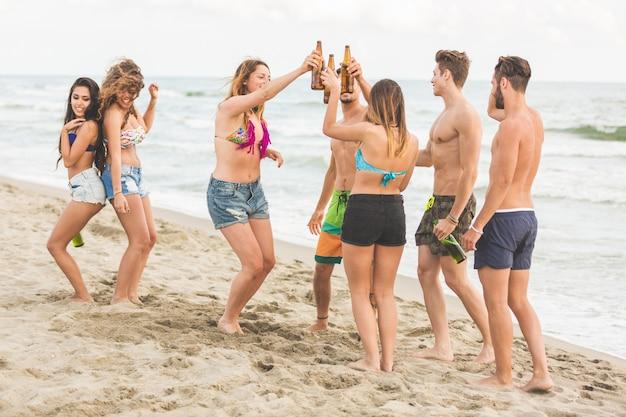 Grupo multirracial de amigos organizando una fiesta en la playa.