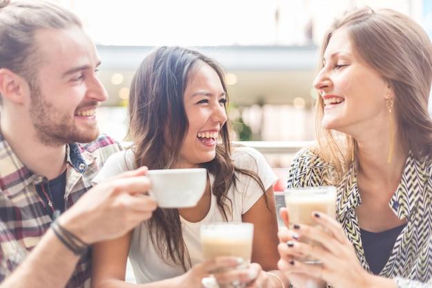 Grupo multirracial de amigos tomando un café juntos.