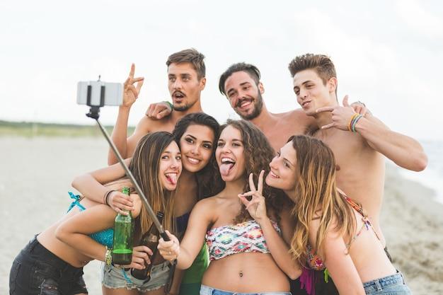 Grupo multirracial de amigos tomando selfie en la playa.